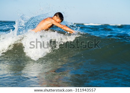 Teenager  boy enjoying a swimming in the sea. - stock photo