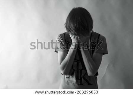 Teenager boy having his hands on his face.B&W picture. - stock photo