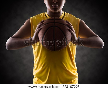 Teenager boy holding a basket ball, Isolated on-a black - stock photo