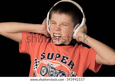 teenager boy in headphones with loud music scared on a dark background - stock photo