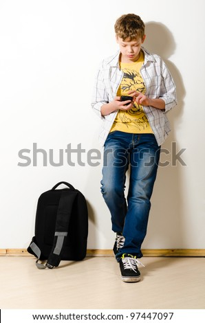 teenager boy is using phone at school - stock photo