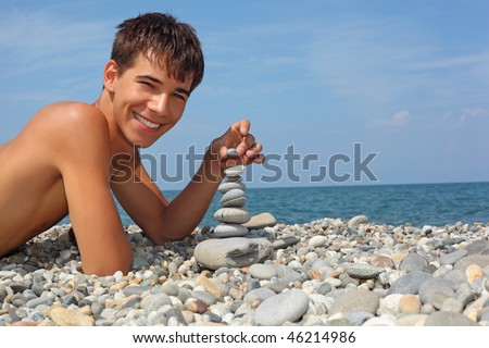 teenager boy lying on stony seacoast, creates pyramid from pebble - stock photo