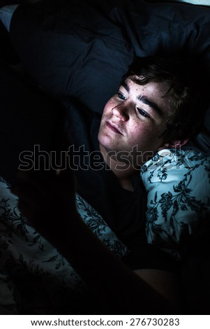 Teenager boy on computer tablet in his room late at night. - stock photo