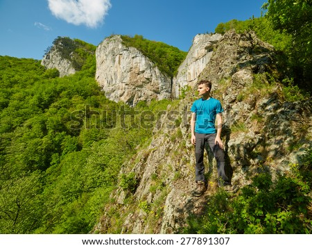 Teenager boy posing on the high mountains in a sunny spring day - stock photo