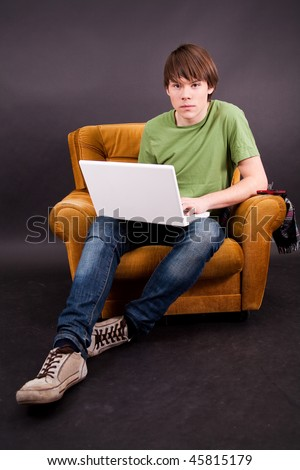 Teenager boy sit on an old armchair with a white laptop - stock photo