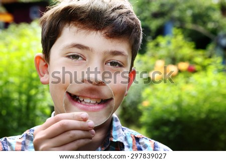 teenager boy smile and grimace with magnifying glass - stock photo