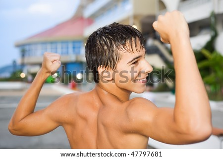 teenager boy standing near hotel on resort in evening, teenager boy with naked torso, shows muscles - stock photo