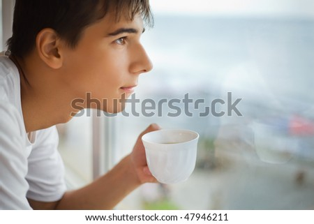 teenager boy with cup in hand looking out of window in morning, focus on cup - stock photo