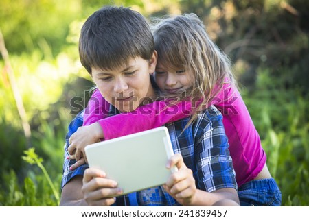 Teenager boy with tablet and his younger sister, outdoors. - stock photo