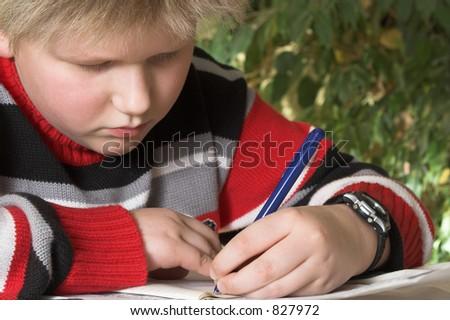Teenager boy writing his homework exercise - stock photo