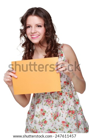 Teenager brunette curly hair girl wearing clothes with floral ornament and showing yellow blank card on Holiday - stock photo