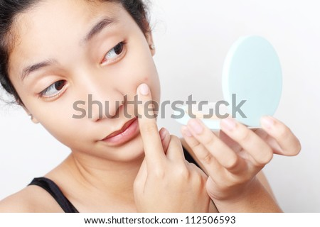 Teenager checking her face for pimple in the mirror. - stock photo