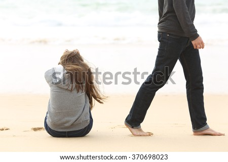 Teenager couple breaking up and ending relation after argument. Boyfriend legs leaves his sad girlfriend and go away - stock photo