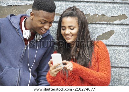 Teenager Couple Sharing Text Message On Mobile Phone - stock photo
