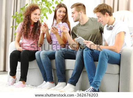 Teenager friends listening to music with different devices on a sofa - stock photo