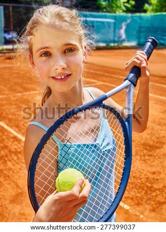 Teenager girl athlete in blue form with racket and ball on  brown tennis court. - stock photo