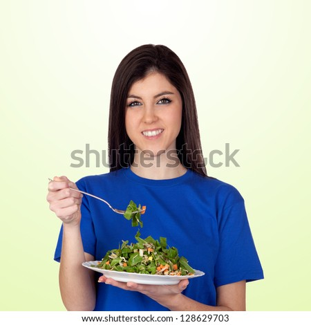 Teenager girl eating vegetables isolated on green background - stock photo