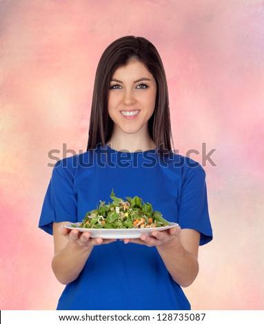 Teenager girl eating vegetables isolated on orange background - stock photo