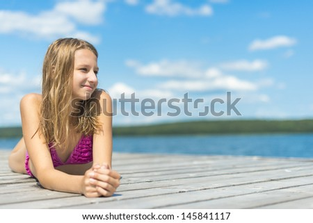 Teenager girl getting rest on the wood pier - stock photo