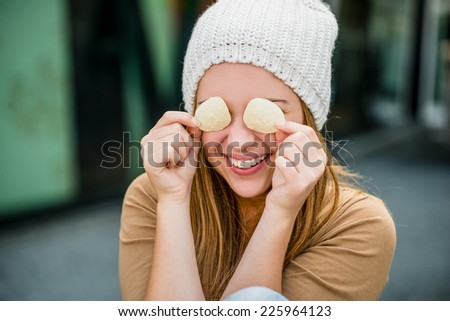 Teenager girl in cap having fun with potato chips on eyes outdoor in street - stock photo