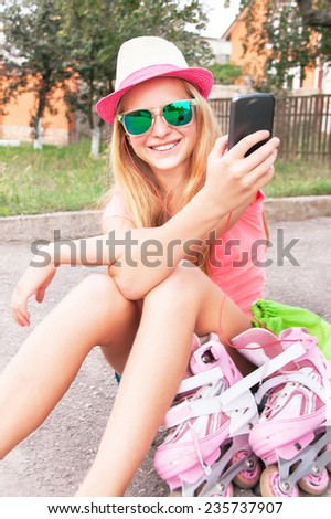 Teenager (girl) is sitting with roller skating shoes (inline skates), using smart phone, listening music with headphone. Teen wearing sunglasses and having fun. Concepts of technology, youth, sport.  - stock photo