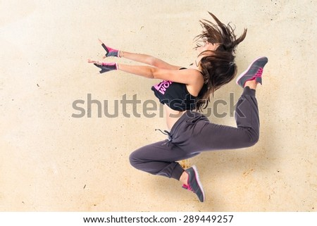 Teenager girl jumping in hip hop style over textured background  - stock photo