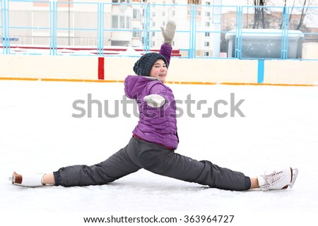 teenager girl on the skating rink make split posing at the end of her rehearsal  show competition program - stock photo