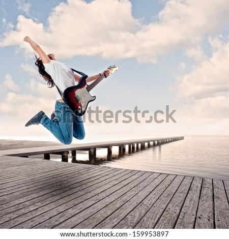 teenager girl playing electric guitar and jumping on a wharf - stock photo