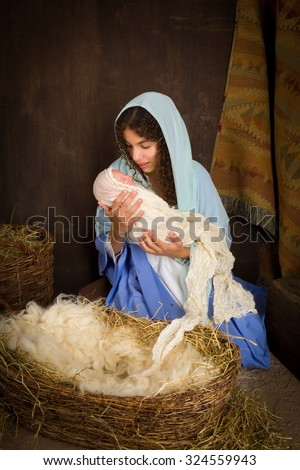 Teenager girl playing the role of the Virgin Mary with a doll in a live Christmas nativity scene (the baby is a doll). - stock photo