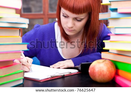 teenager girl, red hair, between piles of books writing - stock photo