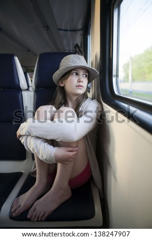 teenager girl sitting in the carriage looking through the window - stock photo