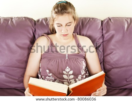 Teenager girl sitting on leather sofa and reading book - stock photo