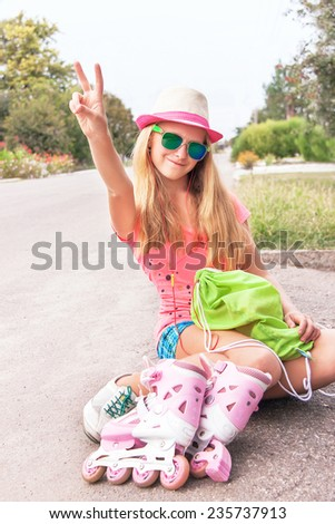 Teenager (girl) sitting with roller skating shoes (inline skates), listening music with headphone. Teen wearing sunglasses, showing victory v hand sign, having fun. Concept of youth, sport, lifestyle. - stock photo