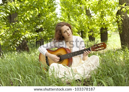 Teenager girl with guitar against green grass - stock photo