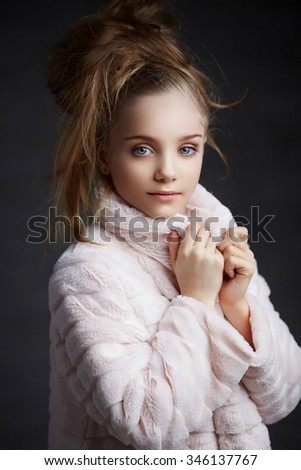 Teenager girl with make up and haircut posing in white coat over grey background. - stock photo