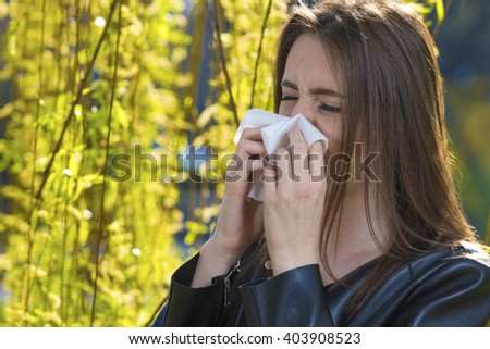 Teenager girl with pollen allergy over flowers - stock photo