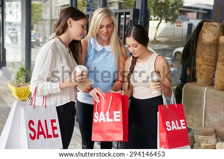 Teenager girls on shopping spree holding sale bags in city - stock photo