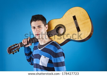 Teenager holding a classic guitar with blue background - stock photo