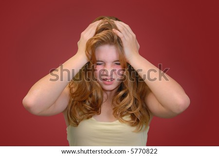 Teenager holding her head with anguished expression on her face - stock photo