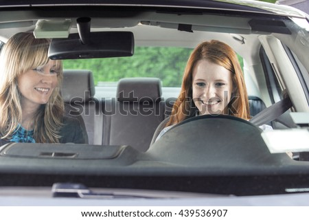 Teenager in car with driving instructor - stock photo