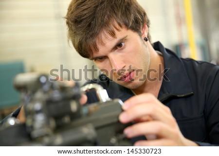 Teenager in professional training, repairing bike engine - stock photo