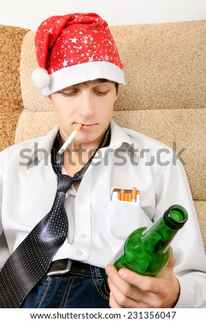 Teenager in Santa Hat with Bottle of the Beer smoking Cigarette - stock photo
