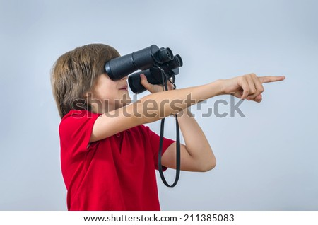 Teenager is looking through reversed binoculars and pointing his finger - stock photo