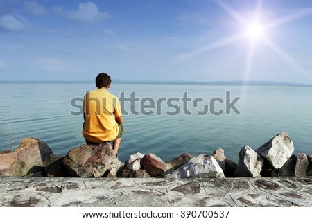 Teenager is sitting alone at Lake Balaton - stock photo