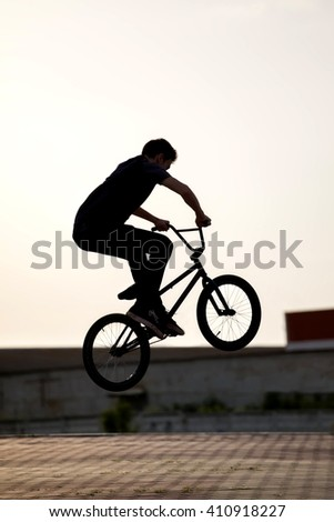 teenager jump on a bicycle outdoors - stock photo