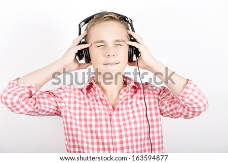 Teenager listens music with headphones on light background - stock photo