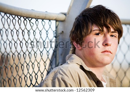 teenager male with natural look sitting against fence looking into camera - stock photo