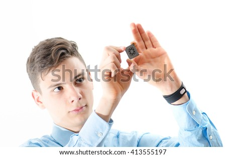 Teenager man concentrated looking at a micro chip isolated on white - stock photo