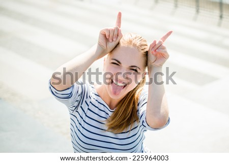 Teenager portrait - smiling girl has fun and pretends she is devil - stock photo