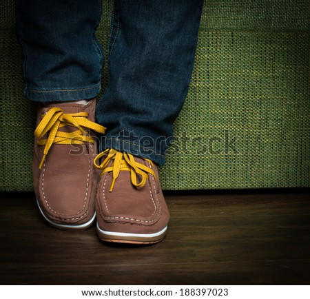 Teenager posing her jeans and shoes, sitting on a green sofa. - stock photo